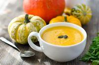 Pumpkin soup with pumpkins on wooden background